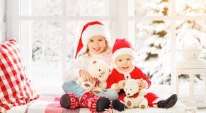 孩子兄弟和姐妹笑和坐冬天窗口圣诞节 图库摄影