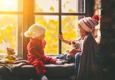孩子兄弟和秋天的姐妹赞赏的窗口 免版税图库摄影