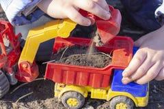 孩子充当有沙子的街道;他在翻斗车玩具装载地球 免版税库存图片