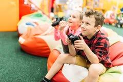 孩子充当比赛控制台,愉快的童年 免版税库存照片