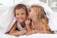孩子共享他们下面的被子秘密 免版税库存图片