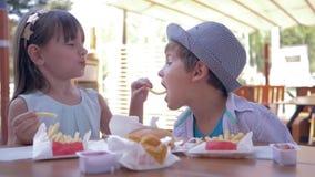 孩子关心,哺养快餐的可爱的孩子坐在街道咖啡馆的桌上 股票视频