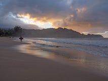 孩子冲浪者离开海洋的藏品bodyboard在日落 免版税库存图片