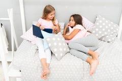 孩子准备上床 宜人的时间舒适卧室 女孩长的头发逗人喜爱的睡衣放松读的书 对书满意 免版税库存照片