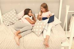 孩子准备上床 宜人的时间舒适卧室 逗人喜爱的睡衣放松的女孩长发读了书 对书满意 库存照片