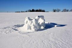 孩子创造的雪堡垒的遗骸在多雪的领域、森林和蓝天背景的明亮的太阳下在冬天  免版税库存照片