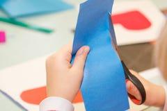 孩子删去了纸 孩子参与针线 免版税图库摄影