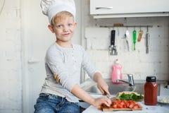 孩子厨师在厨房里在家烹调 健康的食物 免版税库存图片