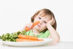 孩子吃一棵红萝卜 免版税库存图片