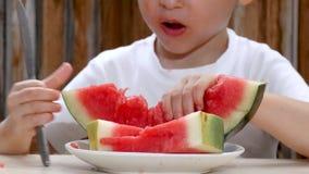 孩子吃从板材的一个西瓜 特写镜头 影视素材