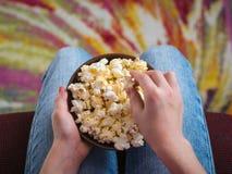 孩子吃从黏土碗的玉米花,坐一把红色椅子 免版税库存图片