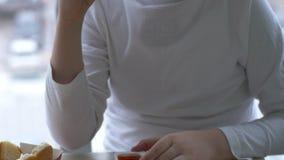 孩子吃午餐在便当咖啡馆 男孩在停车场和都市风景背景中喝柠檬水并且吃汉堡包  影视素材