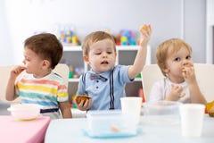 孩子吃午餐在日托中心 吃在幼儿园的孩子 图库摄影