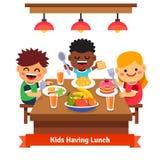 孩子吃晚餐在家幼儿园  免版税库存照片