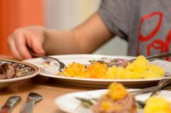 孩子吃汤用他的手,您能看到桌镀和男孩` s手 库存图片