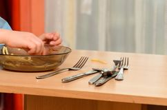 孩子吃汤用他的手,您能看到桌镀和男孩` s手 免版税库存照片