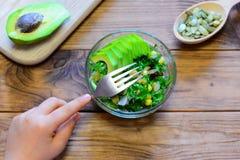 孩子吃沙拉 孩子在他的手上拿着一把叉子 沙拉用新鲜的鲕梨,莴苣叶子,装玉米于罐中 免版税库存照片
