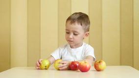 孩子吃着一个苹果并且谈话,当坐在桌上时 股票录像