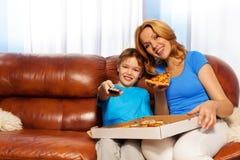 孩子吃薄饼的电视频道和母亲 免版税库存照片