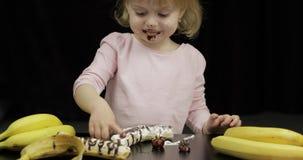 孩子吃香蕉、草莓用熔化巧克力和打好的奶油 影视素材