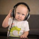 孩子听到在耳机的音乐 免版税库存照片
