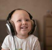 孩子听到在耳机的音乐 免版税库存图片