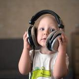 孩子听到在耳机的音乐 库存图片
