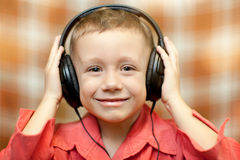 孩子听到在耳机的音乐 库存照片