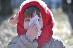 孩子吹他的在餐巾的鼻子 库存图片