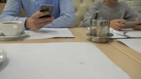 孩子和一个人使用与在桌上的一个手机,等待在咖啡馆的命令 特写镜头,4k 股票录像