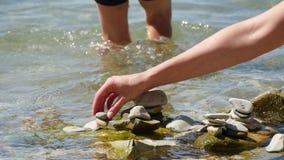 孩子和他的母亲在海滩用他们自己的手,特写镜头上把小卵石放 影视素材