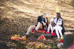 孩子和全家的秋天时尚 妈妈、爸爸和两个孩子一顿野餐的在秋天用苹果,南瓜 家庭我 免版税库存照片