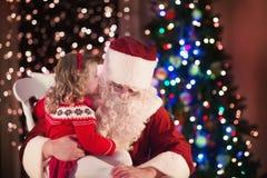 孩子和圣诞老人在火地方圣诞前夕的 免版税库存图片