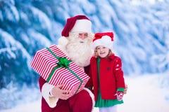 孩子和圣诞老人有圣诞节礼物的 免版税图库摄影