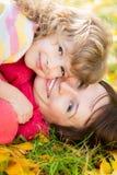孩子和妇女在秋天公园 免版税库存照片