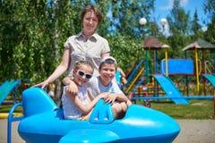 孩子和妇女在蓝色平面吸引力在城市公园,愉快的家庭观念,暑假飞行 图库摄影