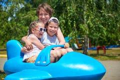 孩子和妇女在蓝色平面吸引力飞行在城市公园,愉快的家庭,暑假概念 库存图片