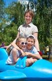 孩子和妇女在蓝色平面吸引力飞行在城市公园,愉快的家庭,暑假概念 库存照片