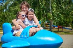 孩子和妇女在蓝色飞机吸引力飞行在城市公园,愉快的家庭,暑假概念 免版税库存图片