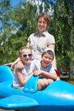 孩子和妇女在蓝色飞机吸引力飞行在城市公园,愉快的家庭,暑假概念 免版税库存照片