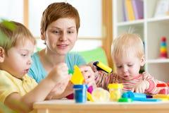 孩子和妇女有五颜六色的彩色塑泥的 免版税库存照片