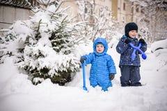 孩子和很多雪 使用户外在家附近的冬天 两个愉快的微笑的兄弟 免版税库存照片