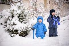 孩子和很多雪 使用户外在家附近的冬天 两个愉快的微笑的兄弟 免版税库存图片