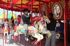 孩子和成人在科尼岛木板走道乘坐科尼岛转盘在月神公园在布鲁克林 库存照片