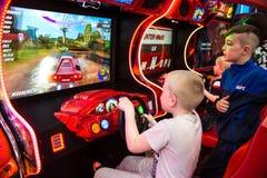 孩子和成人在老虎机,吸引力在购物中心使用 有孩子的家庭有乐趣和戏剧拱廊 免版税图库摄影