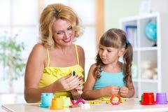 孩子和母亲在托儿所演奏五颜六色的黏土玩具 免版税库存照片