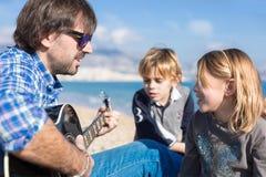 孩子和父亲唱歌歌曲在海滩 库存照片