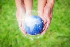 孩子和父亲在手上的拿着行星地球反对绿色spr 库存图片