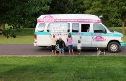 孩子和狗在邻里冰淇凌卡车 免版税库存图片