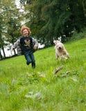 孩子和狗赛跑 免版税库存图片